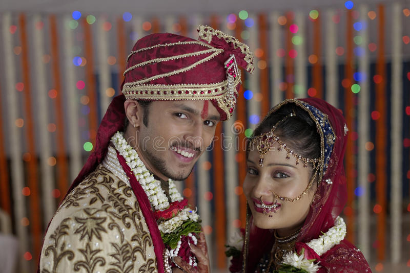 Η ινδική ινδή νύφη & καλλωπίζει ένα ευτυχές χαμογελώντας ζεύγος. στοκ φωτογραφίες