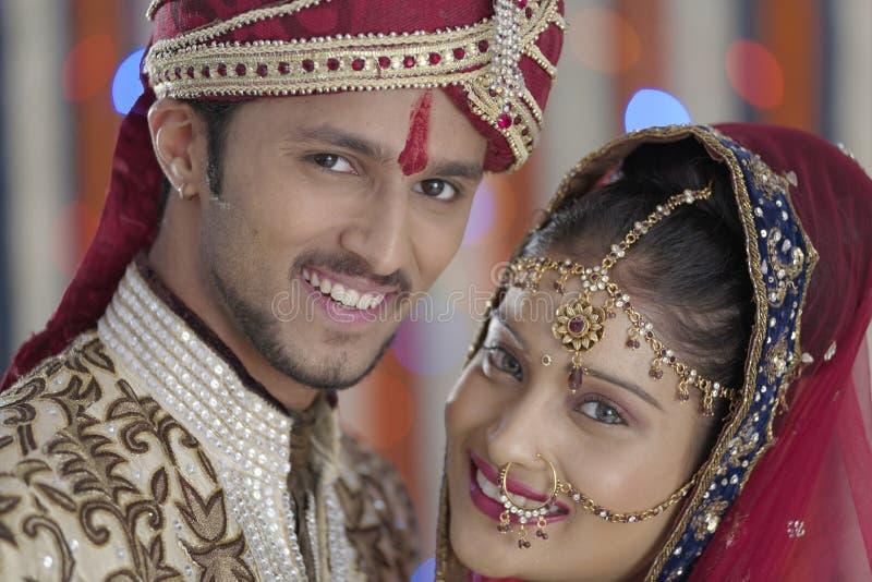 Η ινδική ινδή νύφη & καλλωπίζει ένα ευτυχές χαμογελώντας ζεύγος. στοκ εικόνες