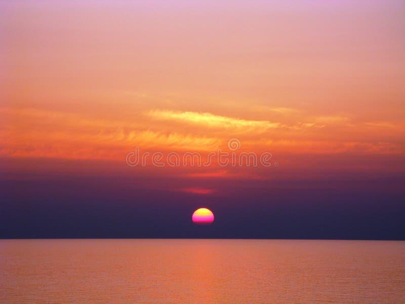 Ηλιοβασίλεμα Ειρηνικών Ωκεανών με τα κόκκινα και πορτοκαλιά σύννεφα, τον πορφυρό και κίτρινο ήλιο στοκ εικόνα