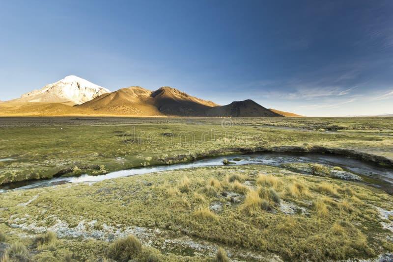 Ηλιοβασίλεμα επάνω από το ηφαίστειο Sajama στη Βολιβία με τον ποταμό στοκ εικόνα με δικαίωμα ελεύθερης χρήσης