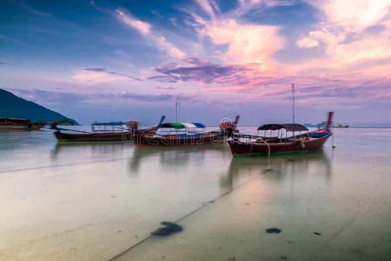 Ηλιοβασίλεμα ζωηρόχρωμο στην παραλία με τη μακριά βάρκα ουρών που σταθμεύουν στοκ φωτογραφίες