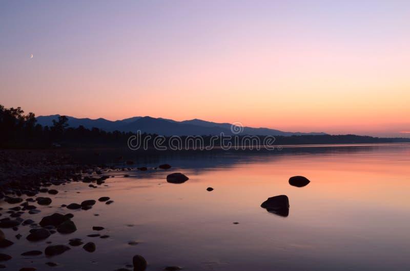 Ηλιοβασίλεμα και ανατολή του φεγγαριού πέρα από τη λίμνη στοκ εικόνες