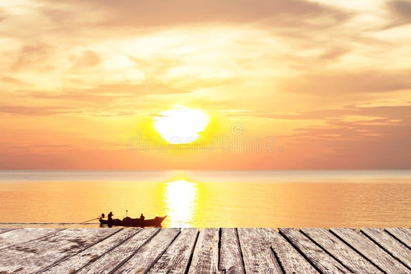 Ηλιοβασίλεμα και ξύλινη διάβαση πεζών στη θάλασσα και τον ουρανό με τη βάρκα στοκ φωτογραφία με δικαίωμα ελεύθερης χρήσης