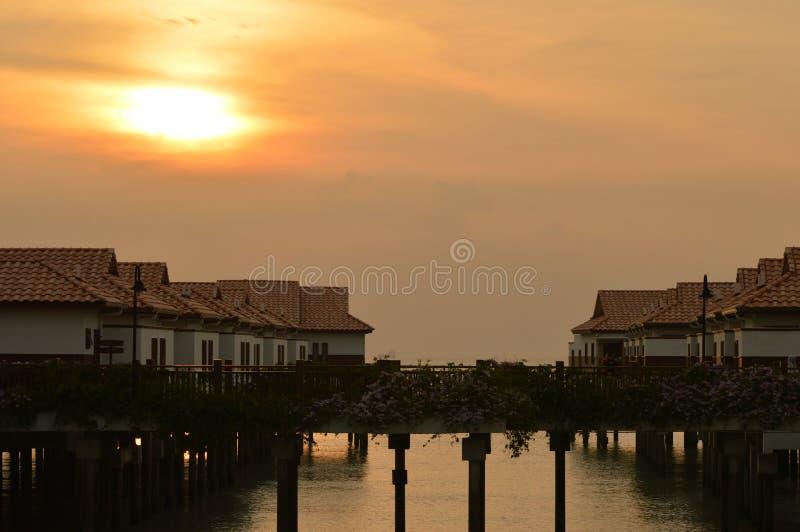 Ηλιοβασίλεμα και σπίτια ανωτέρω - νερό στοκ φωτογραφία