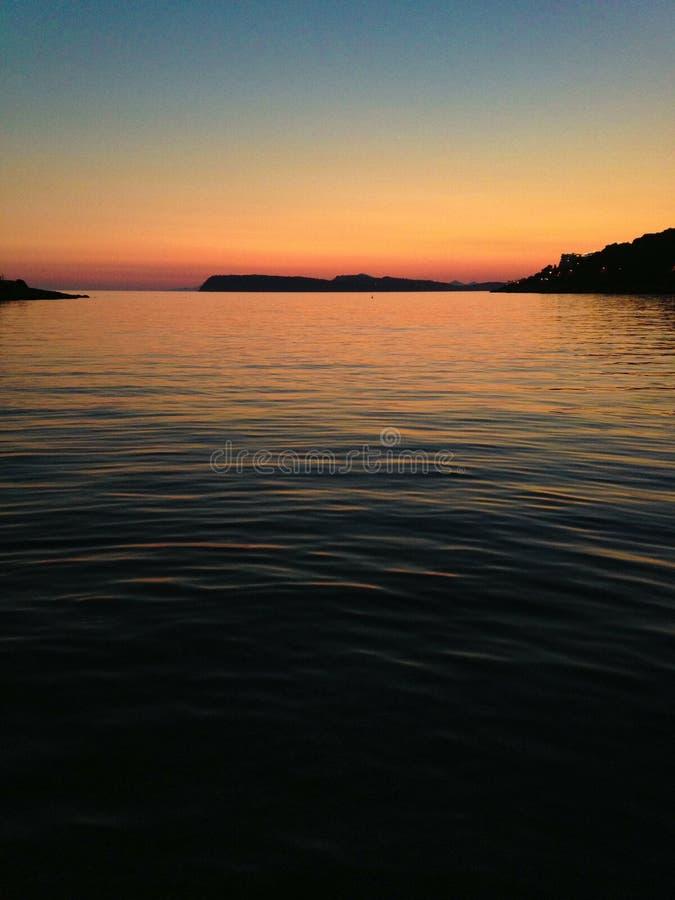 Ηλιοβασίλεμα πέρα από τα ήρεμα νερά στοκ φωτογραφία με δικαίωμα ελεύθερης χρήσης
