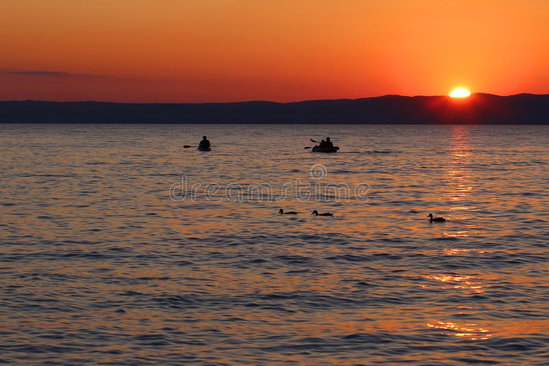 Ηλιοβασίλεμα πέρα από τη λίμνη με τις βάρκες και τις πάπιες στοκ εικόνες
