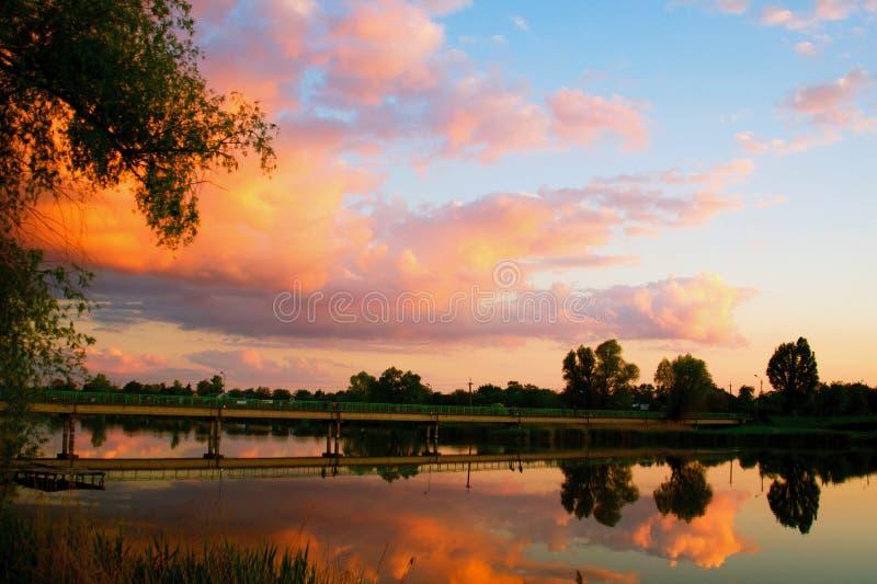 Ηλιοβασίλεμα πέρα από τη λίμνη στο χωριό Άποψη από μια ξύλινη γέφυρα, εικόνα στον πορτοκαλή τονισμό στοκ εικόνες