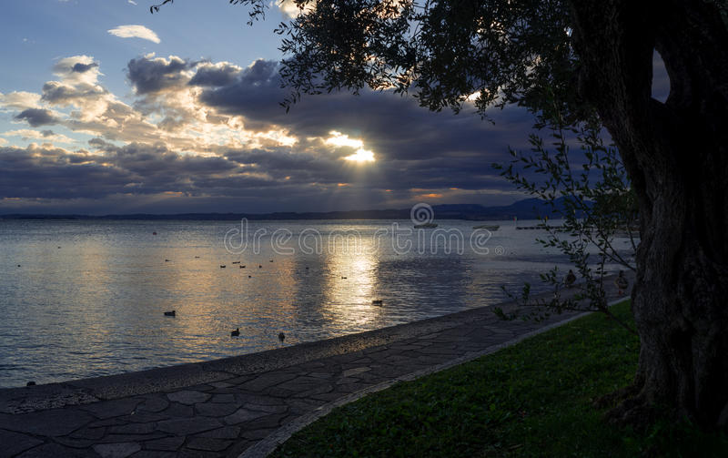 Ηλιοβασίλεμα πέρα από τη λίμνη Garda και το πανόραμα βαρκών ναυσιπλοΐας στοκ εικόνα