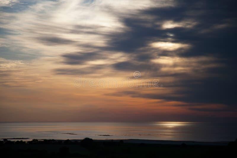Ηλιοβασίλεμα πέρα από τη θάλασσα της Βαλτικής με τα δραματικά σύννεφα στοκ φωτογραφίες