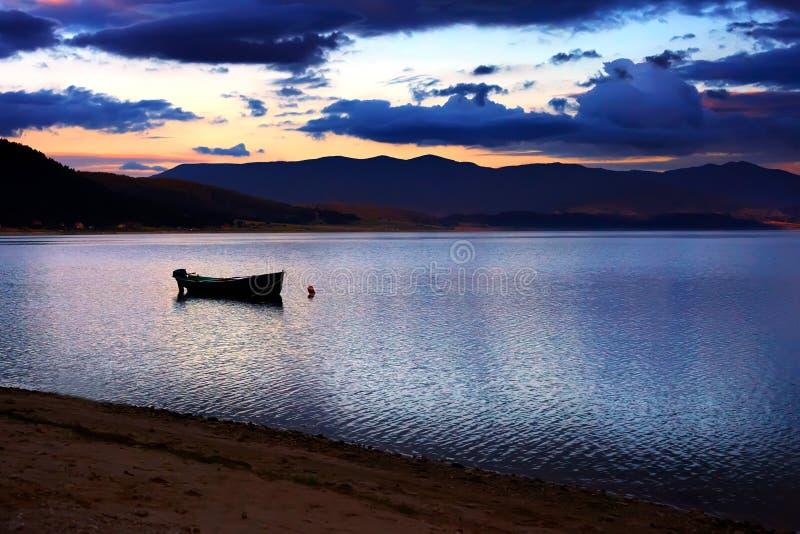 Ηλιοβασίλεμα πέρα από τη μικρή βάρκα στοκ φωτογραφία