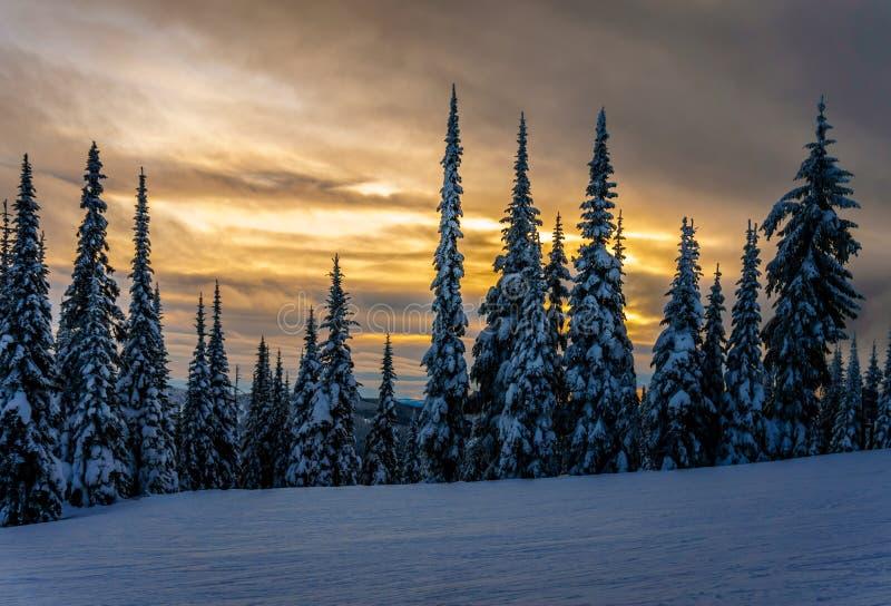 Ηλιοβασίλεμα πέρα από τους λόφους σκι στις αιχμές ήλιων στοκ φωτογραφία