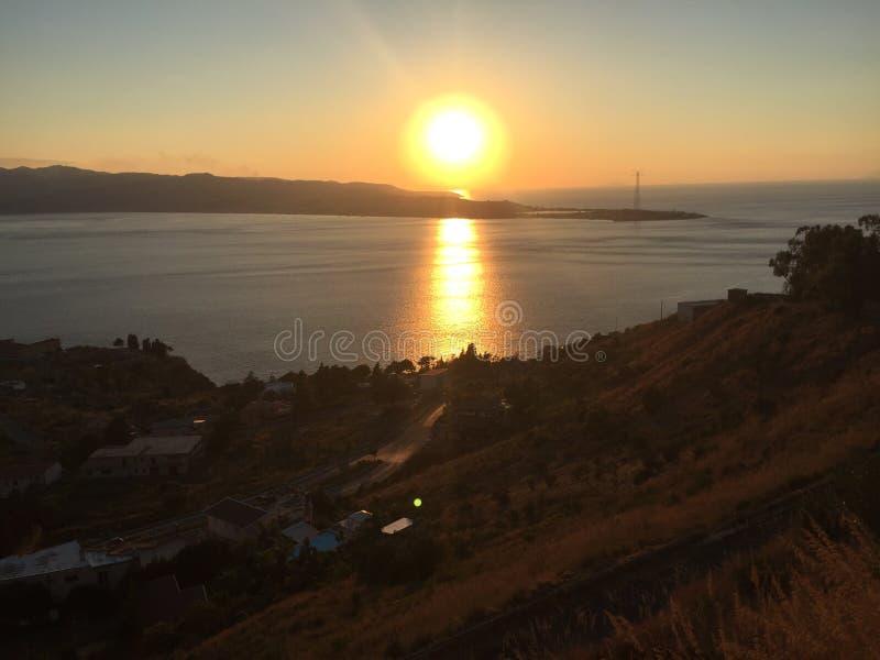 Ηλιοβασίλεμα πέρα από το στενό του Μεσσήνη στοκ εικόνες