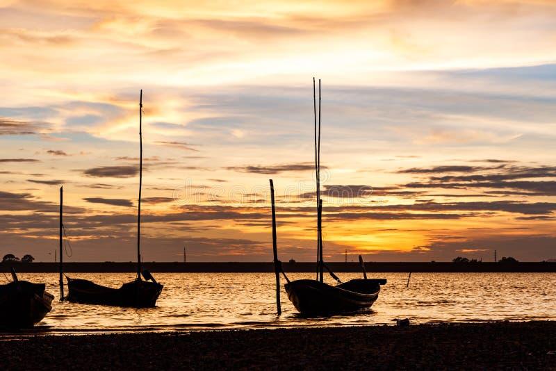 Ηλιοβασίλεμα πέρα από το φράγμα και τη λίμνη με τις βάρκες σκιαγραφιών στοκ εικόνες