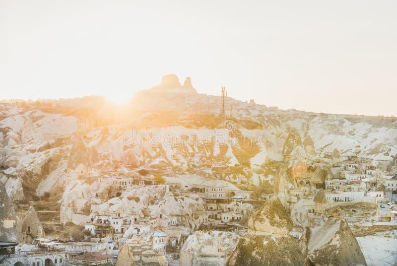 Ηλιοβασίλεμα πέρα από το χωριό Goreme, τα σπίτια σπηλιών και το κάστρο Uchisar, Cappadocia στοκ εικόνα