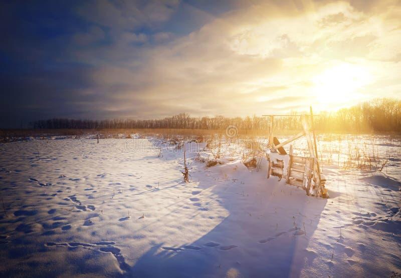 Ηλιοβασίλεμα σε έναν χιονώδη τομέα με τα ίχνη στοκ εικόνα