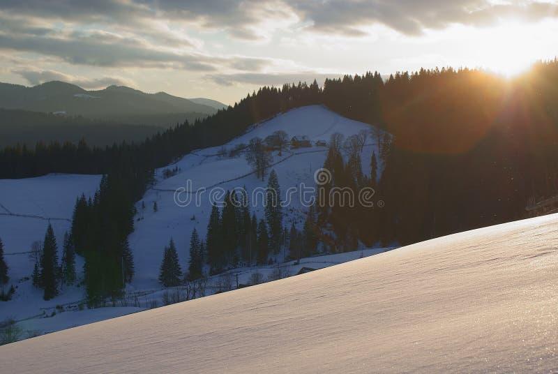 Ηλιοβασίλεμα στα βουνά Χιονώδης κλίση Επαρχία στα ξύλα στοκ φωτογραφία