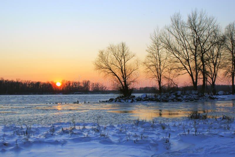 Ηλιοβασίλεμα στην ακτή του μεγάλου ποταμού το χειμώνα στοκ φωτογραφία