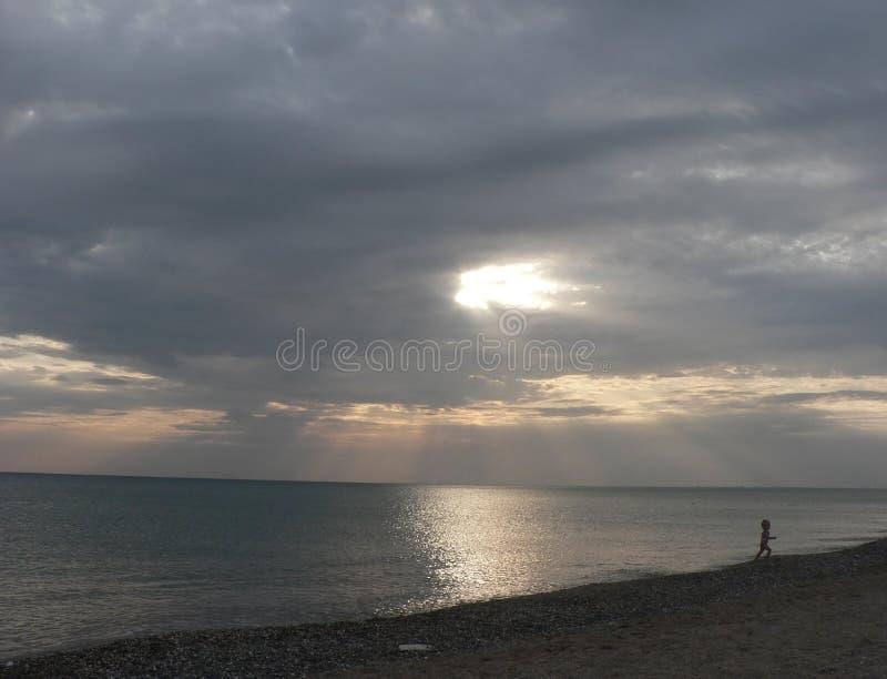 Ηλιοβασίλεμα στη θάλασσα με τον γκρίζο νεφελώδη ουρανό, τρέχοντας αγόρι, ακτίνες του φωτός στοκ εικόνες με δικαίωμα ελεύθερης χρήσης