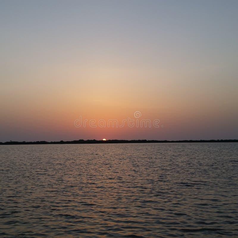 Ηλιοβασίλεμα στο τέλος της ημέρας και συνεδρίαση με τη θάλασσα στοκ φωτογραφία