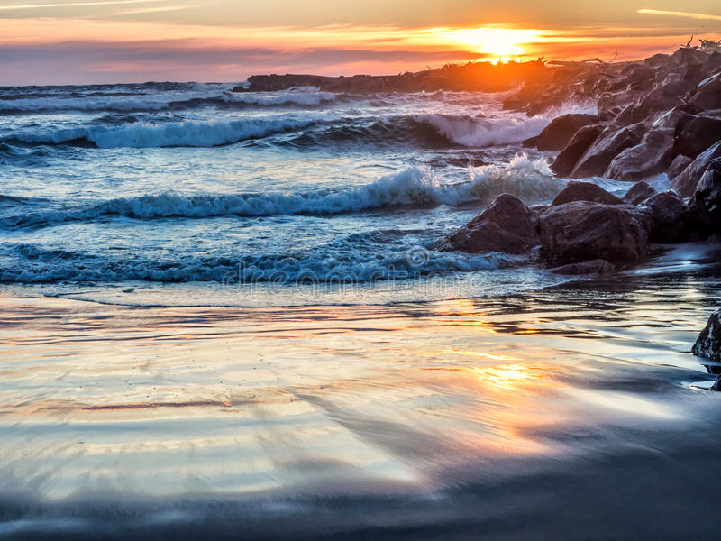 Ηλιοβασίλεμα στο δύσκολο ωκεάνιο λιμενοβραχίονα στοκ φωτογραφία