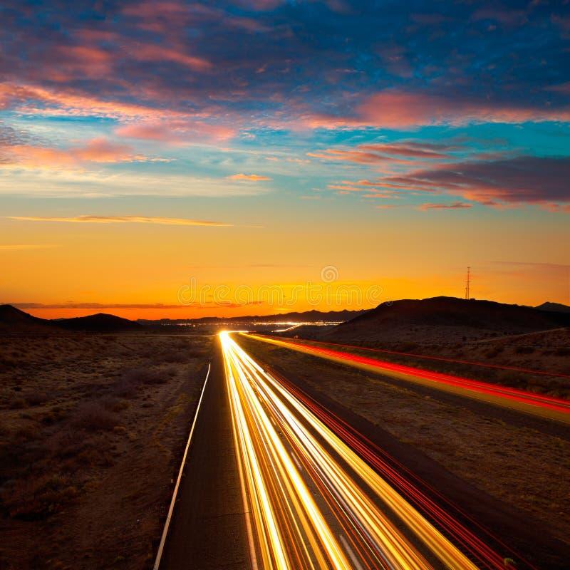 Ηλιοβασίλεμα της Αριζόνα στον αυτοκινητόδρομο 40 με τα ελαφριά ίχνη αυτοκινήτων στοκ εικόνα