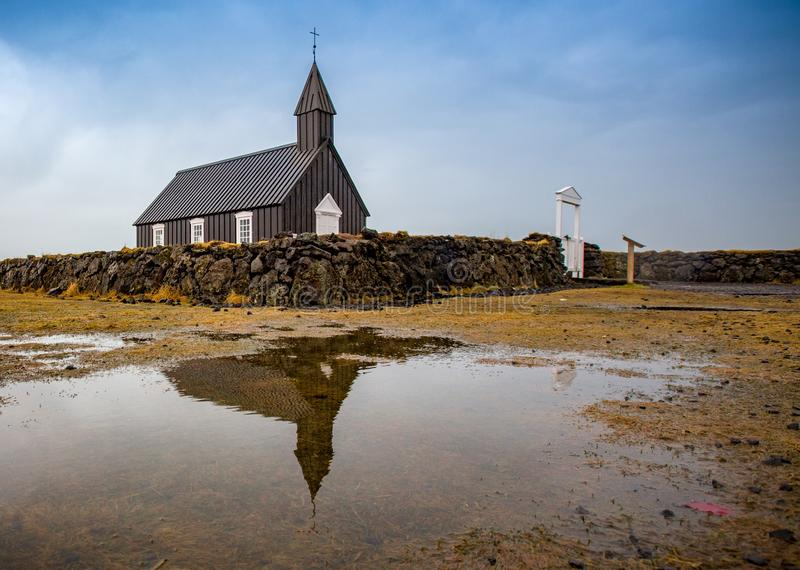 Η ισλανδική εκκλησία ύφους με τον τοίχο πετρών απεικονίζει στη λακκούβα στοκ φωτογραφίες με δικαίωμα ελεύθερης χρήσης