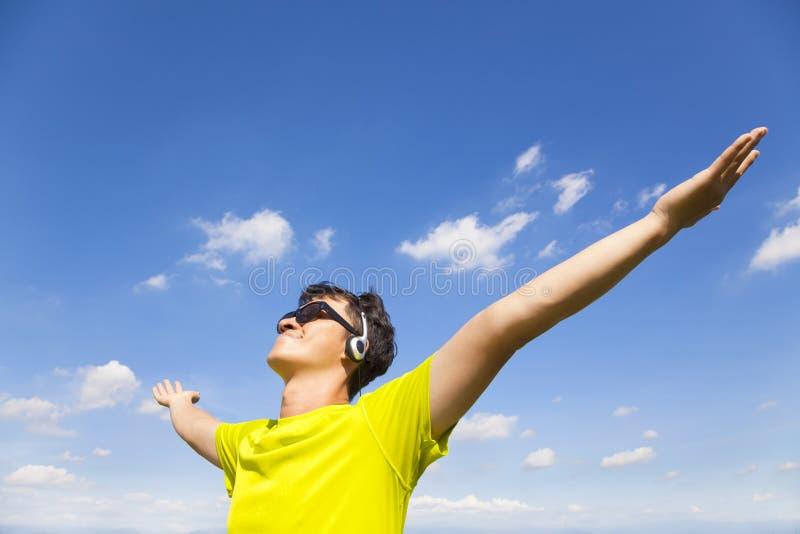 Ηλιόλουστος νεαρός άνδρας που απολαμβάνει τη μουσική με το μπλε ουρανό στοκ εικόνα με δικαίωμα ελεύθερης χρήσης