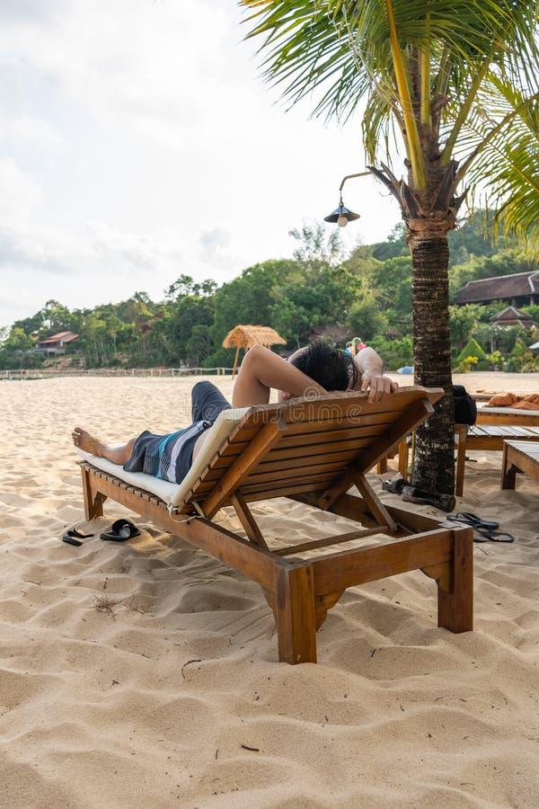 Η κάθετη φωτογραφία του ασιατικού ατόμου χαλαρώνει στην παραλία στοκ φωτογραφία με δικαίωμα ελεύθερης χρήσης