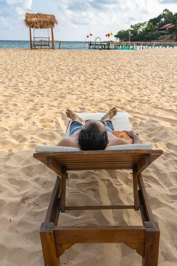Η κάθετη φωτογραφία του ατόμου sunbath και χαλαρώνει στην όμορφη παραλία στοκ εικόνες