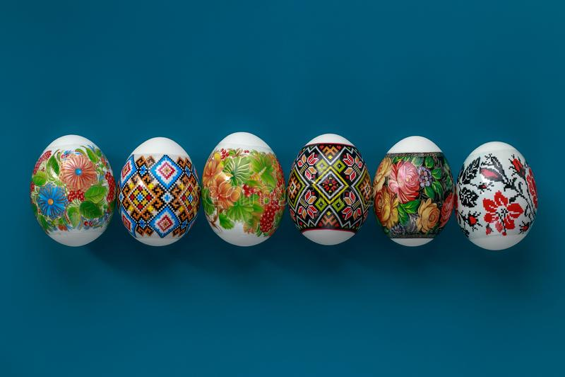 Η κάρτα δώρων με τα ζωηρόχρωμα αυγά Πάσχας κλείνει επάνω στο μπλε υπόβαθρο για το διακοσμητικό σχέδιο ανασκόπηση εορταστική Παράδ στοκ φωτογραφία με δικαίωμα ελεύθερης χρήσης