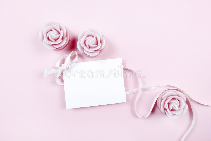 Η κάρτα της Λευκής Βίβλου διακόσμησε με το ρόδινο τόξο και αυξήθηκε scented κερί στοκ εικόνες