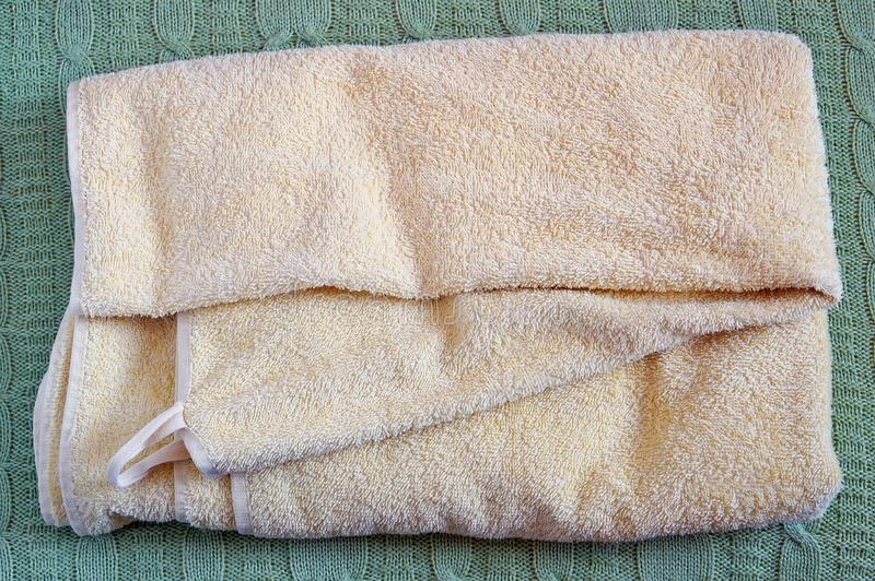 Η κίτρινη πετσέτα λουτρών του Terry βρίσκεται σε ένα πλεκτό μαλλί coverlet κρεβατιών στοκ φωτογραφία με δικαίωμα ελεύθερης χρήσης