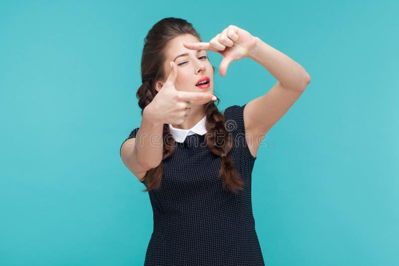 Η καλά ντυμένη νέα γυναίκα που παρουσιάζει σημάδι πλαισίων και κλείνει το μάτι στοκ φωτογραφίες