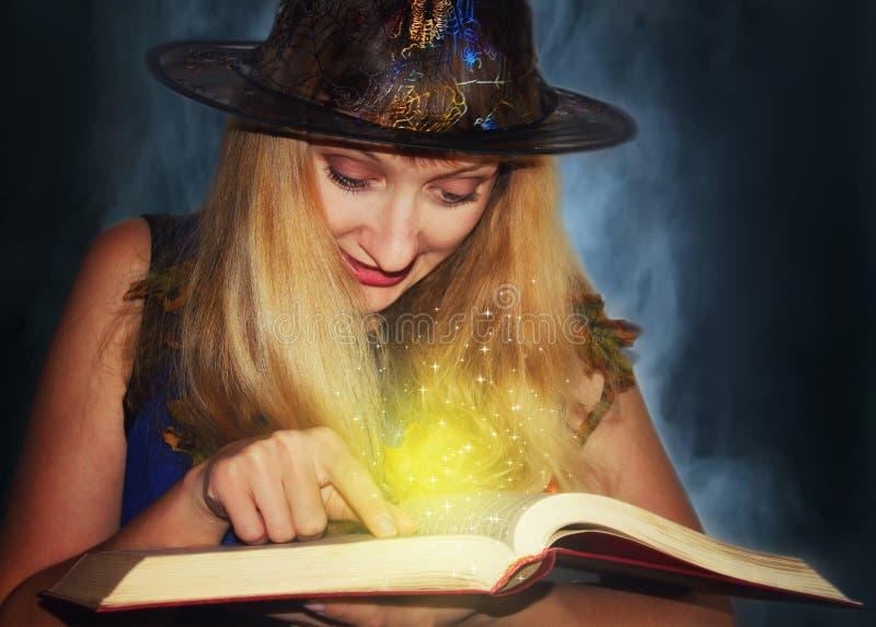 Η καλή μάγισσα στο καπέλο διαβάζει τις μαγικές περιόδους στο βιβλίο στο υπόβαθρο ομίχλης στοκ εικόνα με δικαίωμα ελεύθερης χρήσης