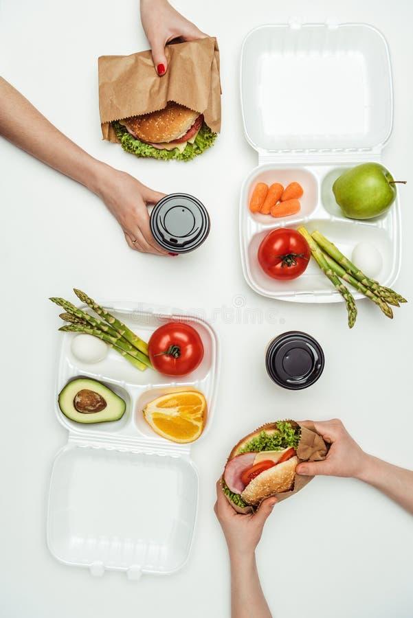 η καλλιεργημένη εικόνα της κατανάλωσης γυναικών παίρνει μαζί τα burgers και τον καφέ κατανάλωσης για να πάει στοκ εικόνες με δικαίωμα ελεύθερης χρήσης