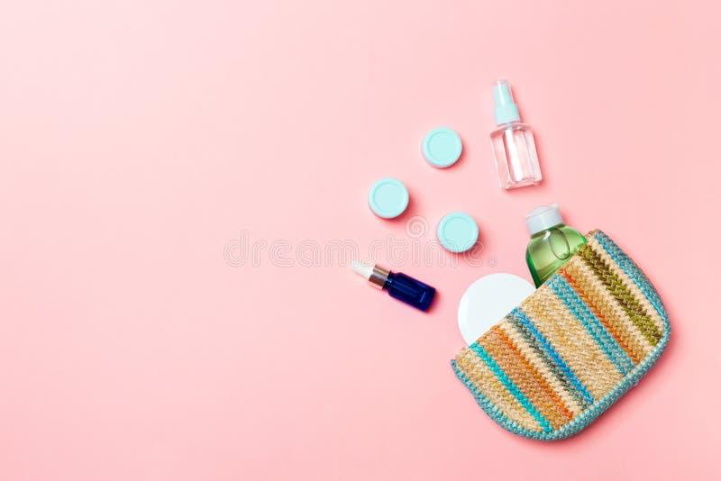Η καλλυντική τσάντα γυναικών με το σύνολο προϊόντος ομορφιάς και bodycare αποβουτυρώνει στο ρόδινο υπόβαθρο κρητιδογραφιών με το  στοκ φωτογραφία