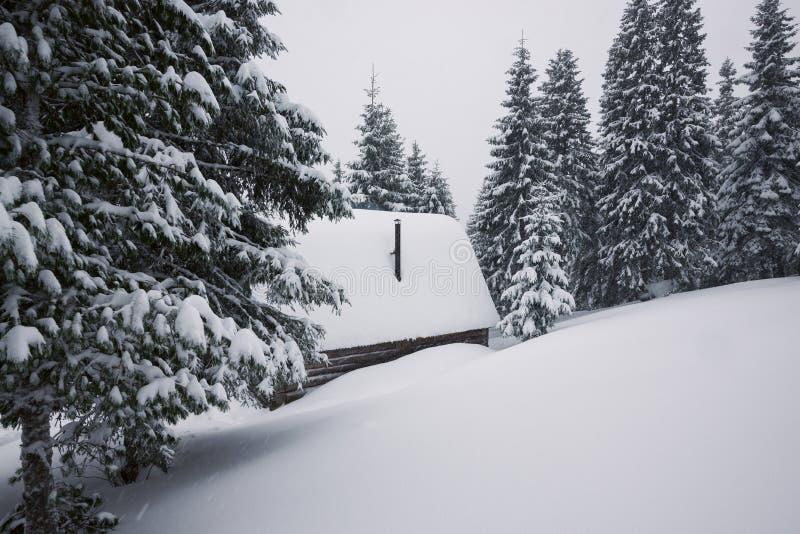 Η καμπίνα κούτσουρων στα χειμερινά βουνά καλύπτεται με το χιόνι στοκ φωτογραφία