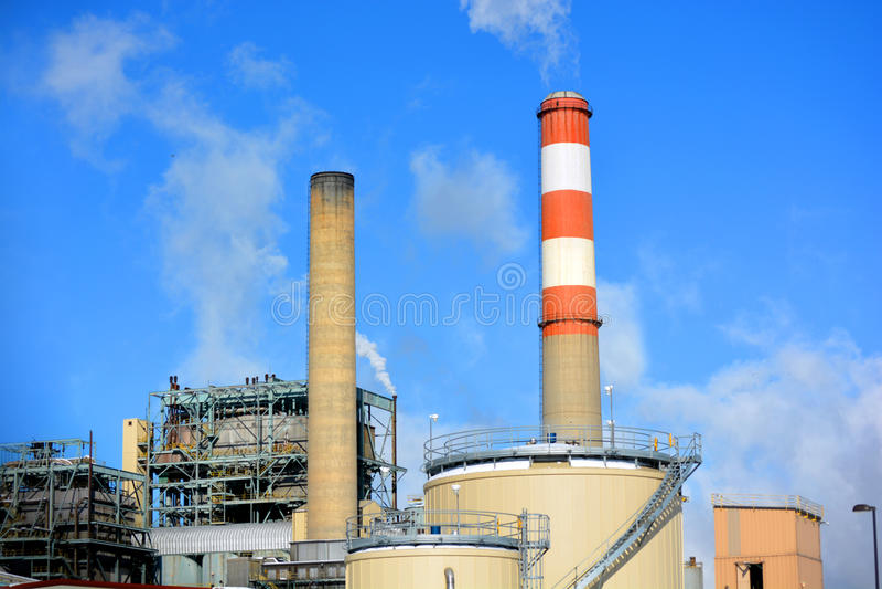 Η καπνοδόχος εγκαταστάσεων παραγωγής ενέργειας ορυκτού καυσίμου άνθρακα με τα κόκκινα και άσπρα χρωματισμένα λωρίδες εκπέμπει τη  στοκ φωτογραφία με δικαίωμα ελεύθερης χρήσης
