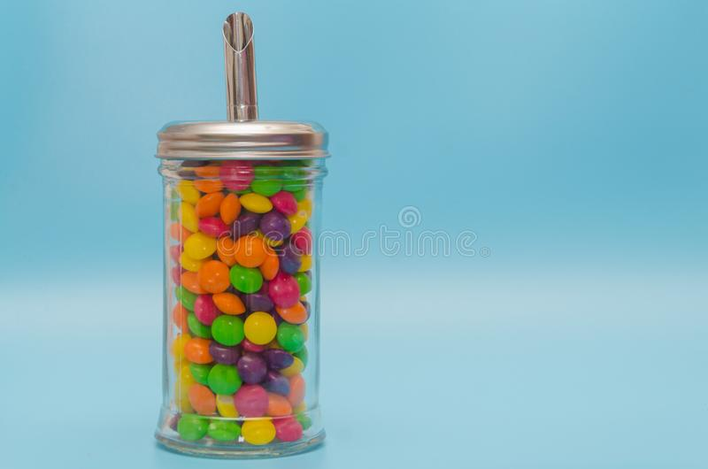 Η καραμέλα καραμελών στο κύπελλο ζάχαρης, κλείνει - επάνω στο μπλε υπόβαθρο στοκ φωτογραφία