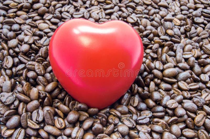 Η καρδιά αριθμού είναι μεταξύ των ψημένων φασολιών καφέ Τα αποτελέσματα του καφέ και της καφεΐνης στην καρδιά λειτουργούν, κτύπος στοκ εικόνα με δικαίωμα ελεύθερης χρήσης