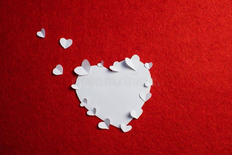 Η καρδιά διαμόρφωσε τη Λευκή Βίβλο και πολλές μικρότερες καρδιές σε το στο κόκκινο υπόβαθρο κόκκινος αυξήθηκε στοκ φωτογραφία με δικαίωμα ελεύθερης χρήσης