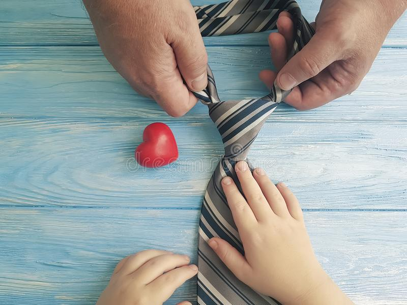 η καρδιά εκμετάλλευσης κορών μπαμπάδων και παιδιών χεριών ημέρας πατέρων ` s δένει στο μπλε ξύλινο υπόβαθρο στοκ εικόνες