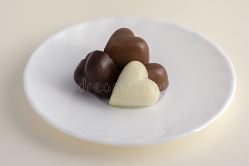 Η καρδιά τα γλυκά σοκολάτας, το καφετί και άσπρο χρώμα, άσπρο πιάτο στοκ φωτογραφία με δικαίωμα ελεύθερης χρήσης