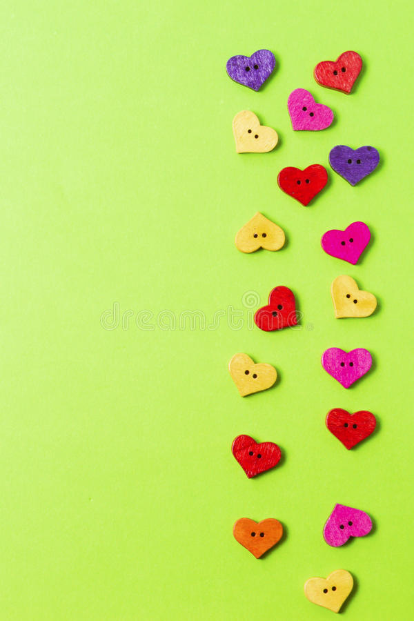 Η καρδιά διαμόρφωσε τα ζωηρόχρωμα ξύλινα ράβοντας κουμπιά στο υπόβαθρο πρασινάδων ως πλαίσιο Διάστημα αντιγράφων για το κείμενο Τ στοκ εικόνα με δικαίωμα ελεύθερης χρήσης