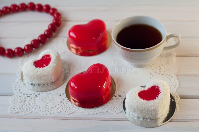 Η καρδιά διαμόρφωσε τα κόκκινα και άσπρα κέικ βάζει στον άσπρο ξύλινο πίνακα κοντά στο φλυτζάνι τσαγιού, χάντρες στοκ φωτογραφίες με δικαίωμα ελεύθερης χρήσης