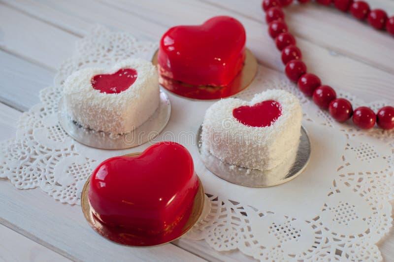 Η καρδιά τέσσερα διαμόρφωσε τα κόκκινα και άσπρα κέικ βάζει στον άσπρο ξύλινο πίνακα στοκ εικόνα με δικαίωμα ελεύθερης χρήσης