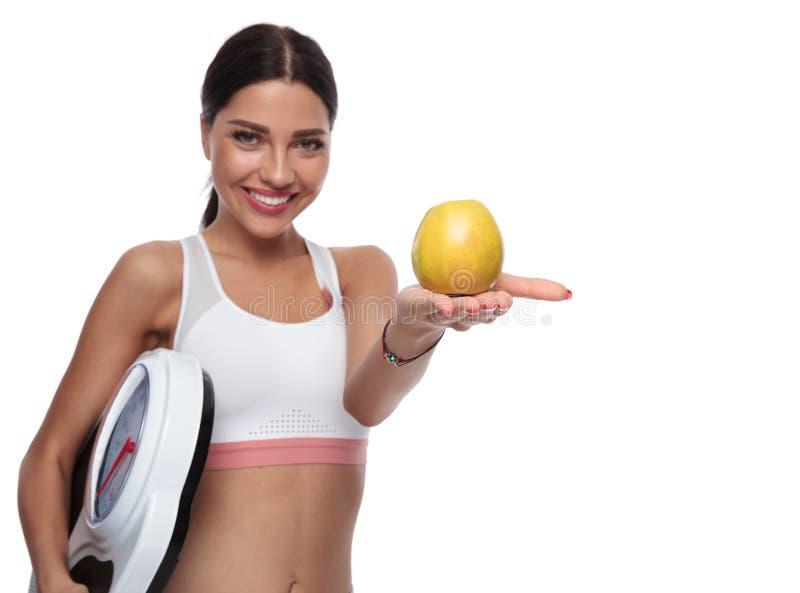 Η κατάλληλη γυναίκα που κρατά μια κλίμακα σας προσφέρει ένα μήλο στοκ φωτογραφίες με δικαίωμα ελεύθερης χρήσης