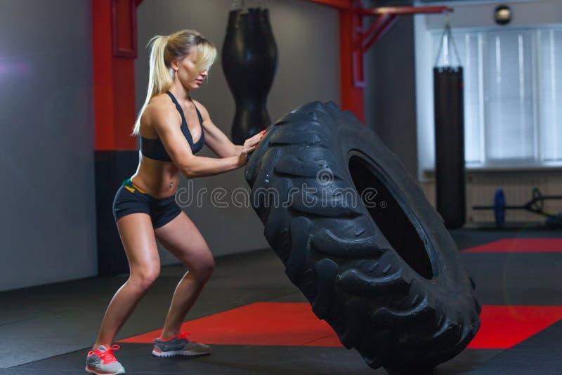 Η κατάλληλη θηλυκή επίλυση αθλητών με μια τεράστια ρόδα, γυρίζοντας και φέρνει στη γυμναστική Γυναίκα Crossfit που ασκεί με τη με στοκ φωτογραφία