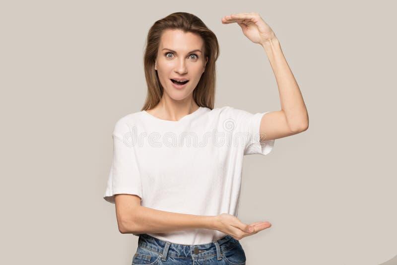Η κατάπληκτη γυναίκα αισθάνεται κατάπληκτη από τη μέτρηση μεγάλων κλιμάκων στοκ φωτογραφία με δικαίωμα ελεύθερης χρήσης