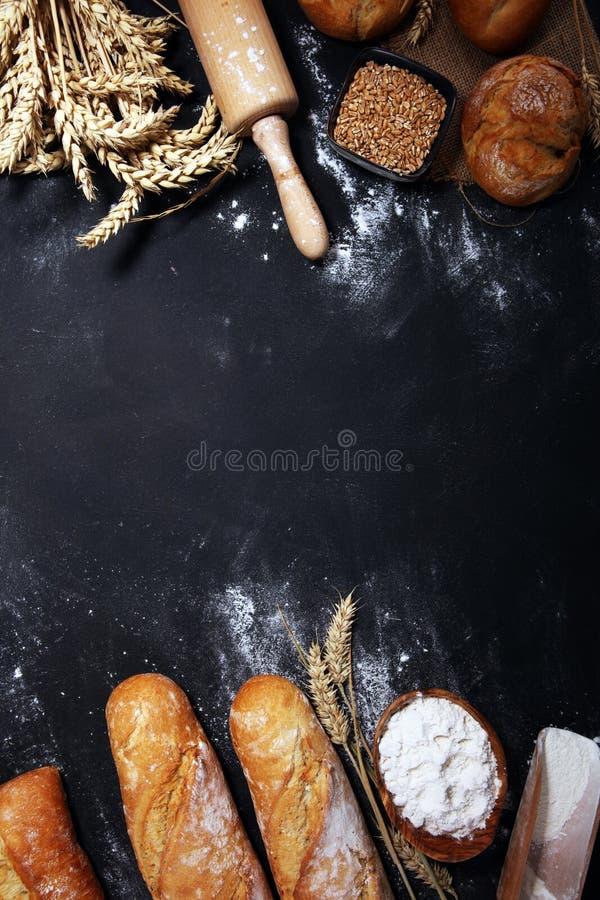 Η κατάταξη του ψημένου ψωμιού και οι ρόλοι ψωμιού στο αγροτικό μαύρο αρτοποιείο παρουσιάζουν το υπόβαθρο στοκ εικόνα με δικαίωμα ελεύθερης χρήσης